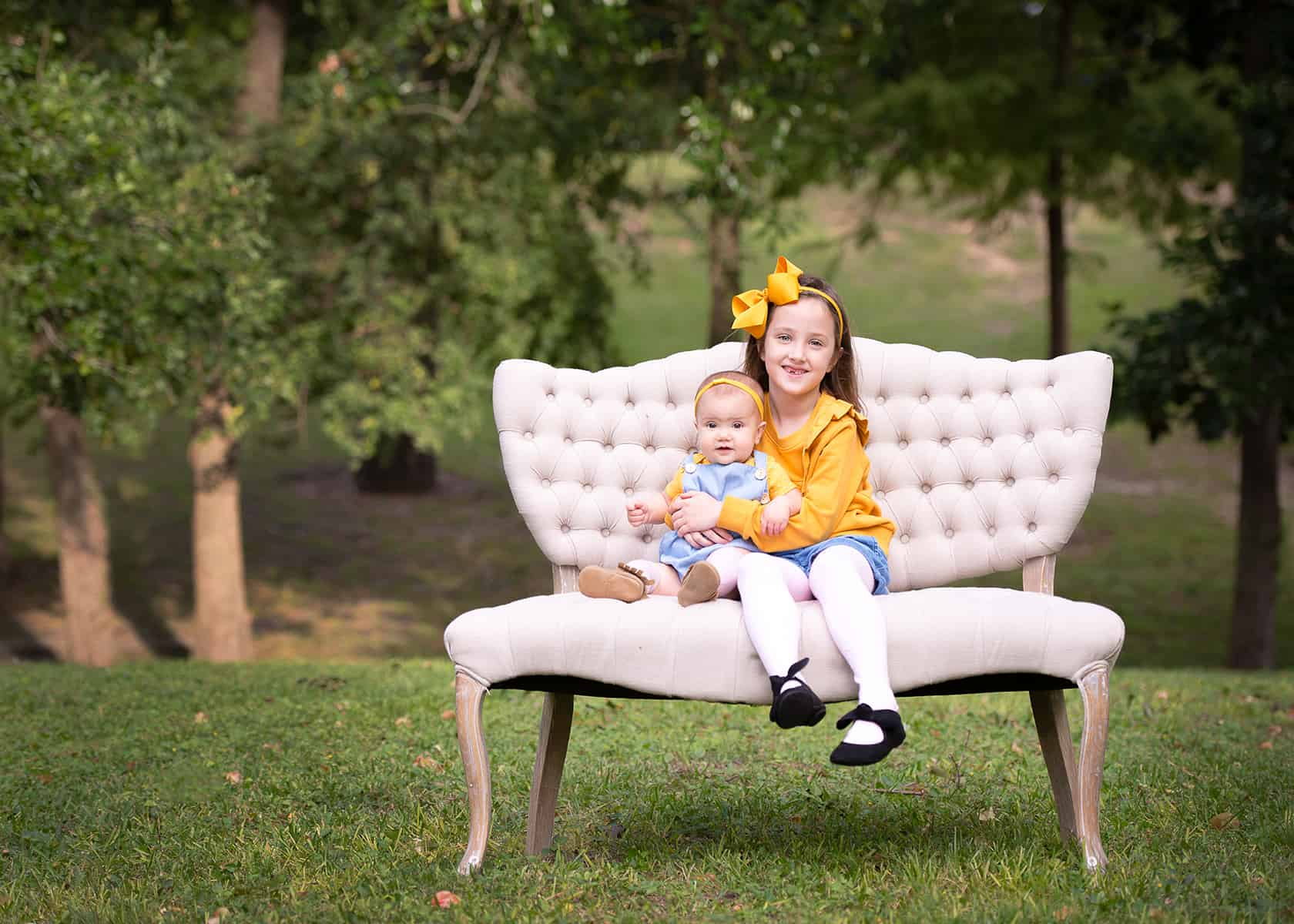 Sisters on a couch in the park wearing yellow for photoshoot