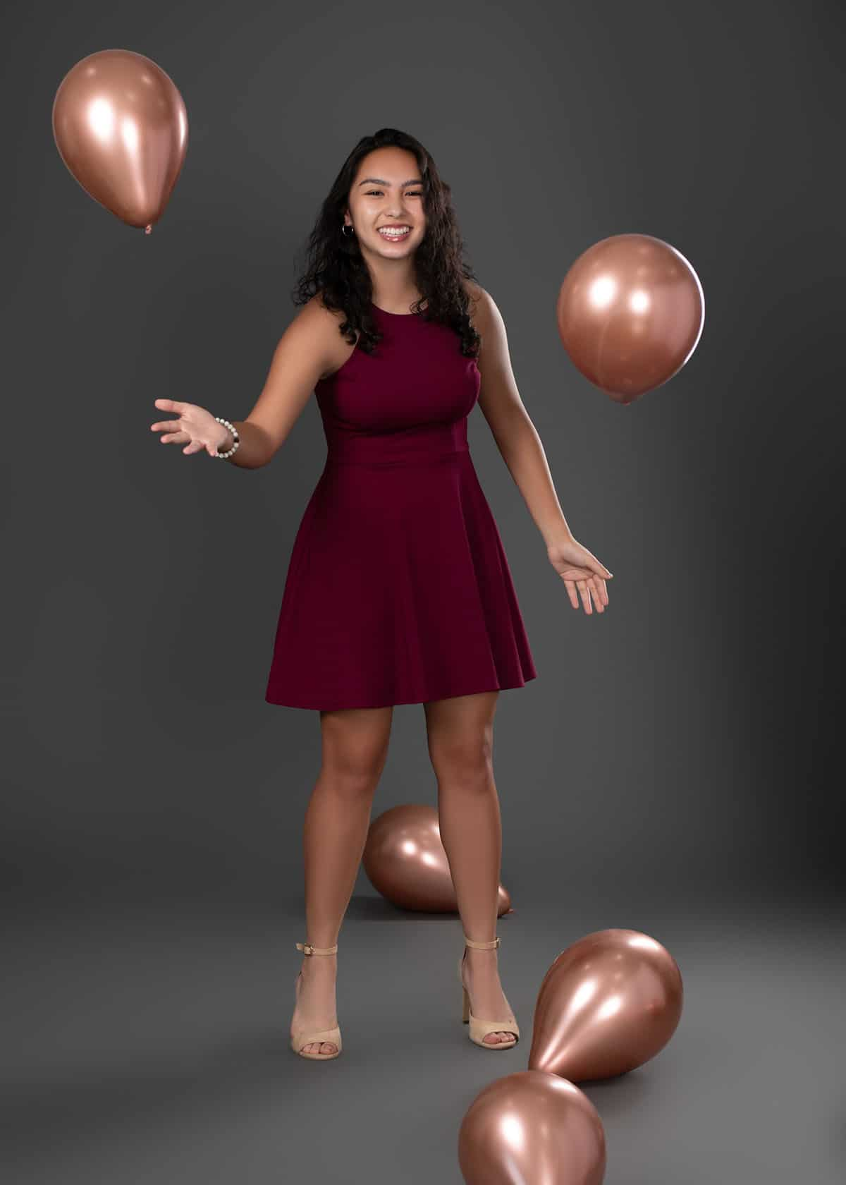 in studio photoshoot senior girl in maroon dress with balloons on gray background